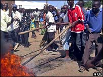 An irate mob burns a tyre in the middle of a road in Homa Bay in Nyanza Province