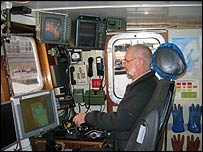 Captain of ship with screens in front of him