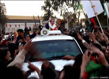 Former Prime Minister Benazir Bhutto waves from her car just seconds before being attacked