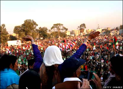 Benazir Bhutto waves to thousands of supporters at a campaign rally on 27 December 2007.