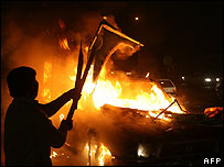 Demonstrator stands by burning car in Lahore on 27 December