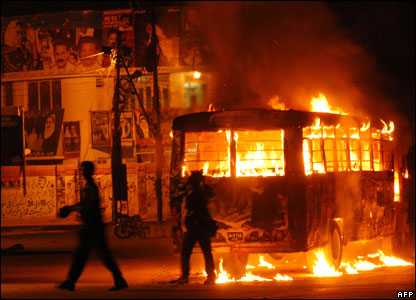 Pakistani pedestrians pass by burning vehicles on a street in Karachi