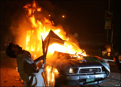 A Pakistani supporter of Benazir Bhutto shouts beside a burning car in Lahore