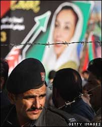 Policeman stands near Bhutto billboard in Rawalpindi, 27 December