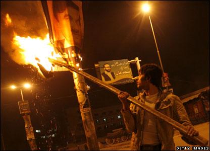 A young man sets a PML-Q banner alight in Rawalpindi