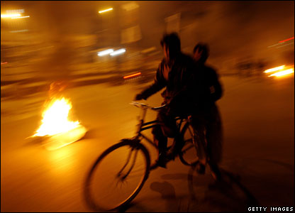 A man cycles past burning tyres in Rawalpindi
