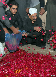Asif Ali Zardari and his and Benazir's son Bilawal scatter rose petals on her grave