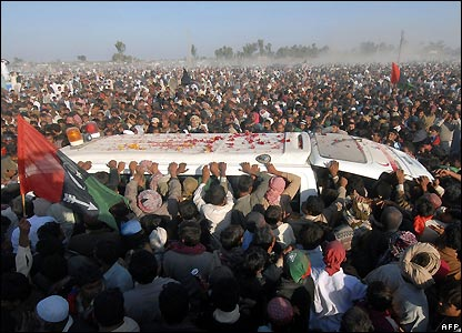 Mourners surround ambulance bearing Benazir Bhutto's coffin to her funeral