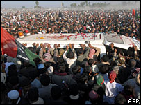 Benazir Bhutto supporters surround an ambulance carrying her coffin, 28 December 2007
