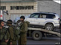 Israeli soldiers stand in front of the attackers' jeep