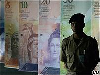 Soldado frente a reproducciones de la nueva moneda venezolana