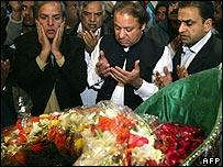 Nawaz Sharif (centre) praying at Ms Bhutto's grave
