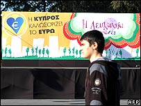 Boy walking past a banner promoting the euro in Cyprus