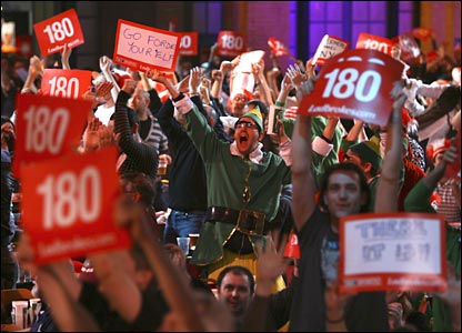 Fans at the Alexandra Palace salute another 180 score.