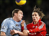 Richard Dunne challenges Fernando Torres