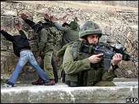 Israeli soldiers search Palestinians in Hebron in the West Bank
