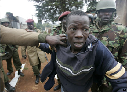 Police officers detain an opposition supporter in Kibera