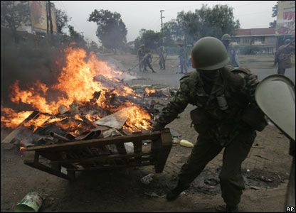 A riot police officer removes a burning barricade during riots in the Kibera slum in Nairobi