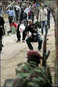 A protester taunts a riot policeman in  Kibera, Nairobi