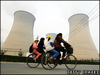 Chinese women cycle past a Beijing power plant (file image)