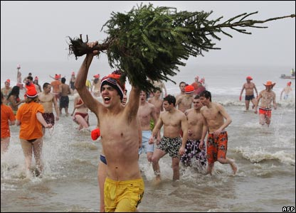 A man in the sea carrying a Christmas tree