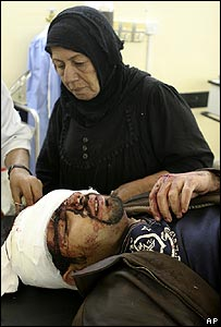 A woman tends to a man wounded in the Baghdad funeral attack on 1 January