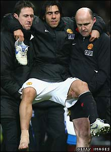 Carlos Tevez is carried away with a suspected ankle injury