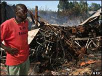 Man stands beside burnt church in Eldoret
