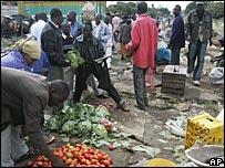 "Kenyan""s buy vegetables at a market in the Kibera slum in Nairobi"