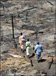 People walk through a burned out area of Nairobi's Kibera slums, which was razed to the ground after days of rioting