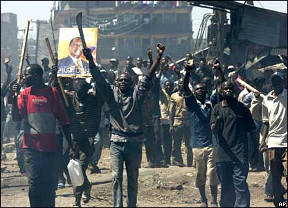 Opposition supporters raise machetes and sticks next to a poster of opposition leader Raila Odinga during riots in the Mathare slum in Nairobi