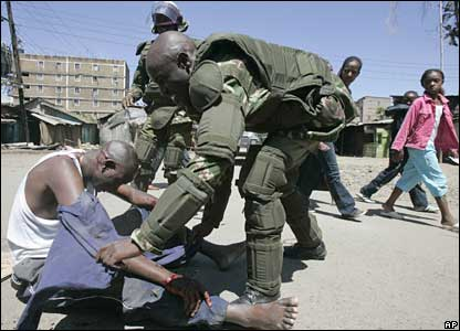 Kenyan riot police help a man who was attacked with machetes during riots in the Mathare slum of Nairobi
