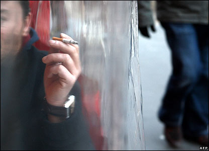 A man smokes at an outside restaurant table in Paris, protected from the weather by a plastic sheet