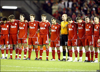The Liverpool players unite for a minute's silence before the match