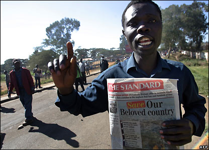 Kibera resident holds up newspaper as he tries to join the Nairobi march