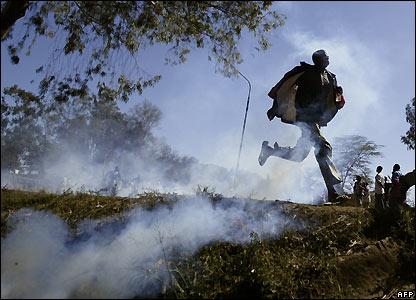 Supporters of Raila Odinga run through tear gas in Nairobi