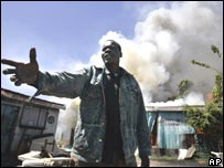 Man stands in front of burning shop in Nairobi