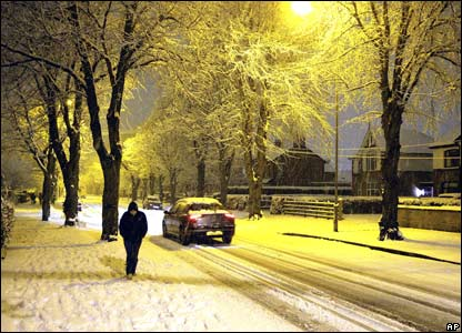 A woman in the snow lit by street lamps on a residential street.
