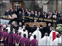 mourners and coffin outside a church