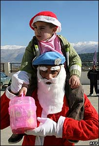 A UN peacekeeper poses in a Santa costume to give out presents in south Lebanon, December 2007