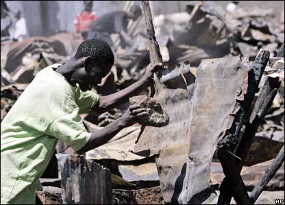 Man picks up corrugated iron from burnt down area of Mathare slum, Nairobi