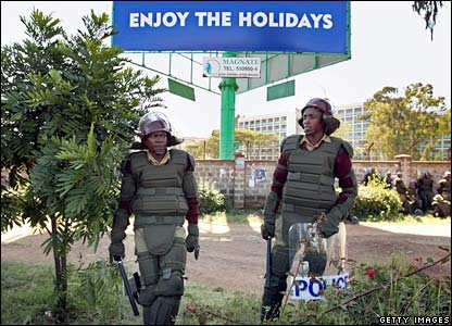 Riot police stand guard under Christmas/New Year message