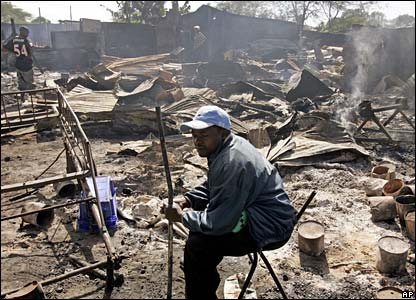 Man sits amid remains of shops in Nairobi's Kibera slum
