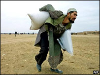 An Afghan man carries sacks of wheat, received as humanitarian aid. File photo