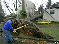 An official ropes off a house damaged by a tree in Sacramento