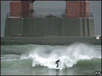 A surfer rides a wave churned by the winter storm underneath the south tower of the Golden Gate Bridge on Friday