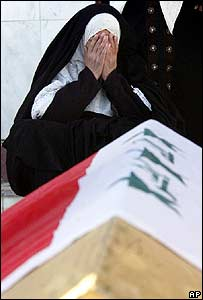 The widow of Riyadh Samarrai grieves beside his coffin