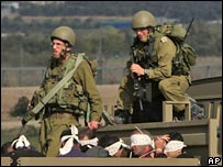 Israeli soldiers guard Palestinian prisoners in the southern Gaza strip