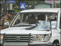 A Sri Lankan police officer looks into the damaged vehicle of minister D.M. Dassanayake  - 8/1/08