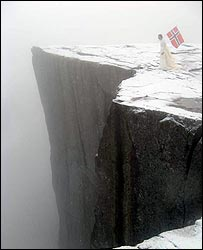 Person with Norwegian flag on cliff near Stavanger